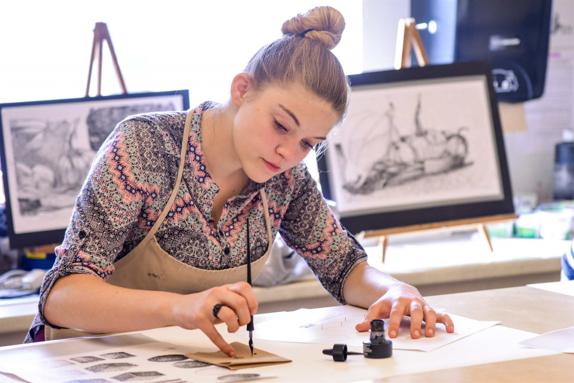 A female student working on a pen and ink drawing in the art studio.